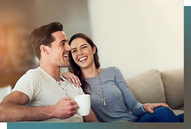 Man and woman sitting on couch. man is holding a coffee mug