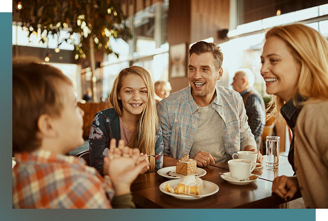 Family of four having coffee and cake in restaurant